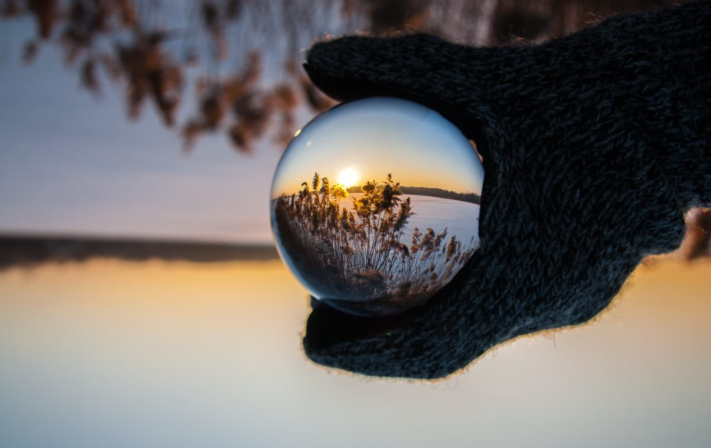 a hand holding a glass sphere that is reflecting the world we see
