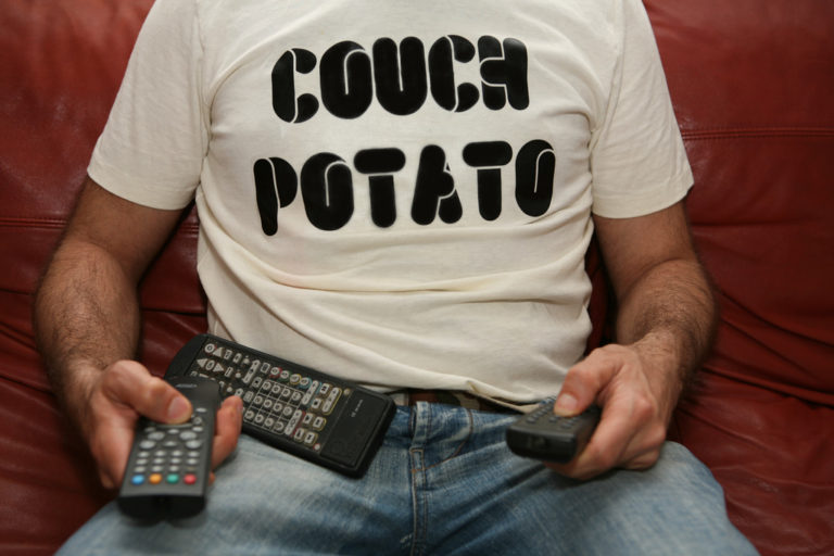 man sitting down in front of TV